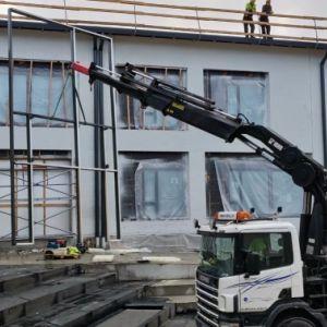 Koulurakennuksen lasiseinän asennus.